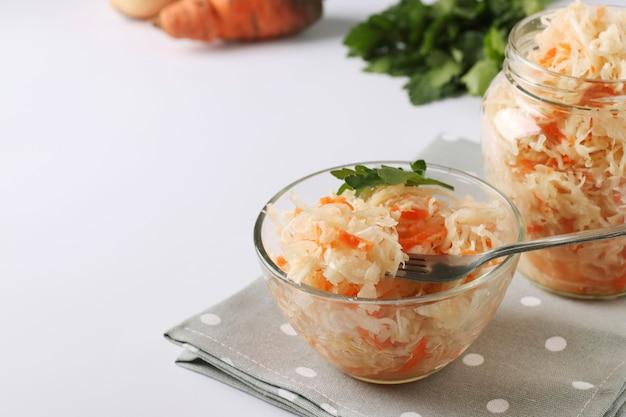 Cibo fermentato, crauti fatti in casa con carote in una ciotola e barattolo su sfondo bianco, primo piano