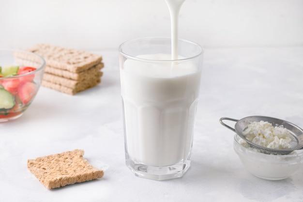 Lo yogurt kefir fermentato viene versato in un bicchiere. concetto di sana colazione