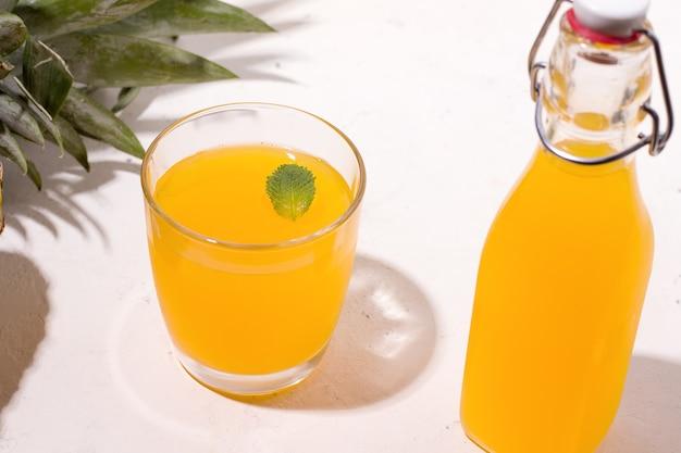 Bevanda estiva di ananas kombucha fermentato in un bicchiere e una bottiglia