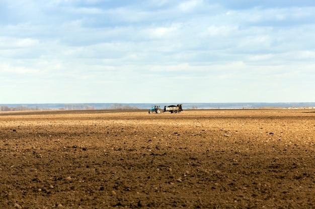 Fecondazione di terreno agricolo campo agricolo su cui il trattore cavalca e fertilizza il terreno primavera il tempo prima della semina