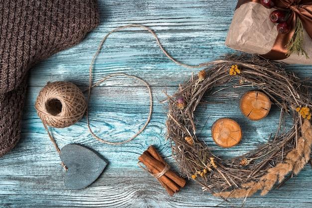 Priorità bassa atmosferica festiva con una corona, un regalo e un cuore su un fondo di legno.