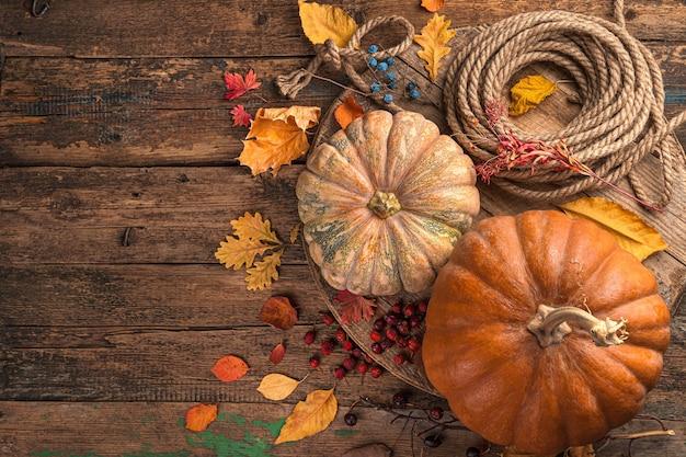 Fondo festivo di autunno delle bacche e del fogliame delle zucche su un fondo di legno marrone