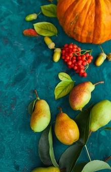 Decorazioni autunnali festive da zucche, pere, foglie, ghiande e bacche su sfondo verde, posa piatta autunnale, composizione autunnale, raccolto, giorno del ringraziamento.