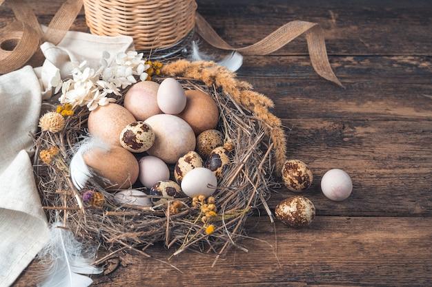 Sfondo festivo con bellissime uova di quaglia e gallina su uno sfondo di legno
