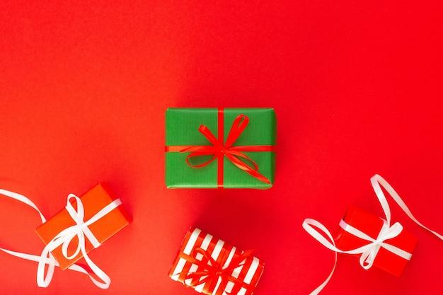 Sfondo festivo con doni colorati, scatole regalo con nastro e fiocco su sfondo rosso, piatto laico, vista dall'alto