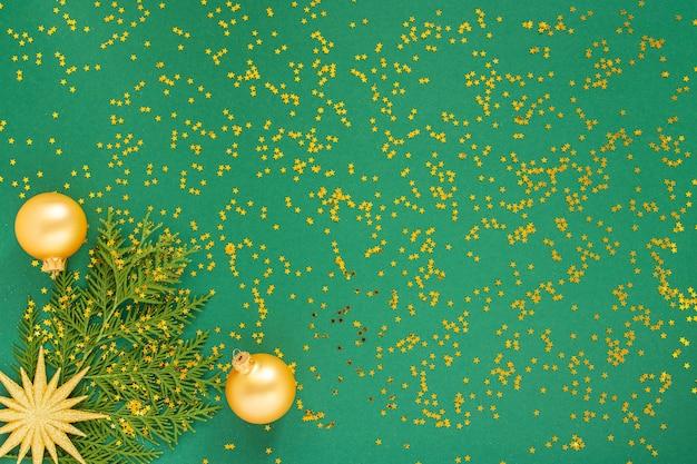 Sfondo festivo con decorazioni, stella d'oro brillante e palle di natale su uno sfondo verde con stelle dorate glitter, vista piana, vista dall'alto, spazio di copia