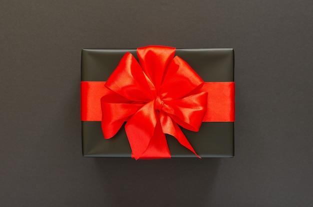 Sfondo festivo con regalo, confezione regalo nera con nastro rosso e fiocco su sfondo nero, concetto di venerdì nero, vista piana, vista dall'alto