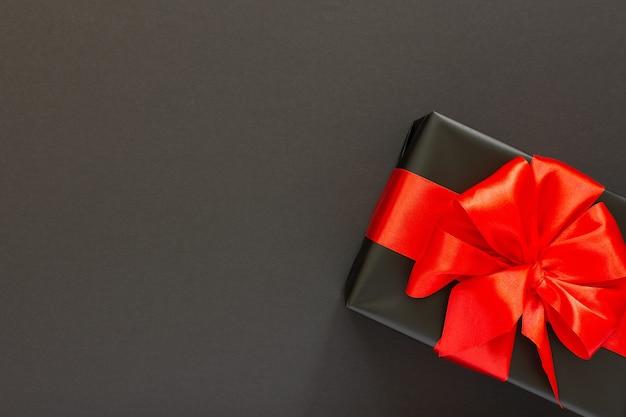 Sfondo festivo con regalo, confezione regalo nera con nastro rosso e fiocco sul nero
