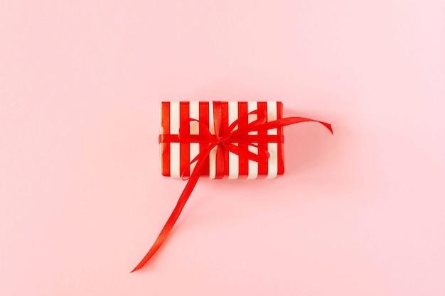 Sfondo festivo con regalo, confezione regalo con nastro e fiocco su carta rosa