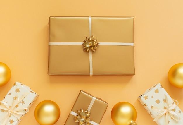 Sfondo festivo con decorazioni in oro, sfondo oro con scatole regalo e palle di natale, vista piana laico e superiore