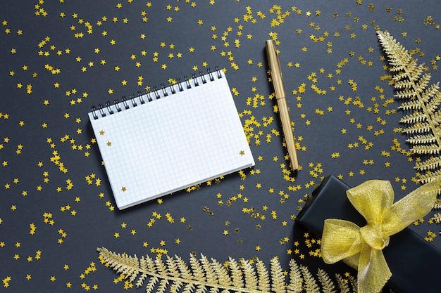Sfondo festivo con decorazioni in oro, foglie di felce dorate lucide e confezione regalo su uno sfondo nero con stelle dorate glitterate, blocco note a spirale aperto e penna, vista piatta, dall'alto