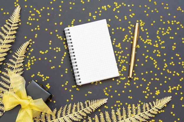 Sfondo festivo con decorazioni in oro, foglie di felce dorate lucide e confezione regalo su sfondo nero con stelle dorate glitterate, blocco note a spirale aperto e penna, disposizione piatta, vista dall'alto