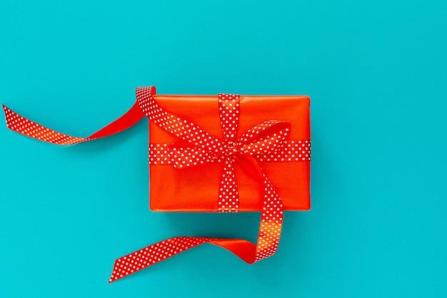 Sfondo festivo con regalo rosso, confezione regalo con nastro e fiocco su sfondo blu turchese, vista piana laico e superiore