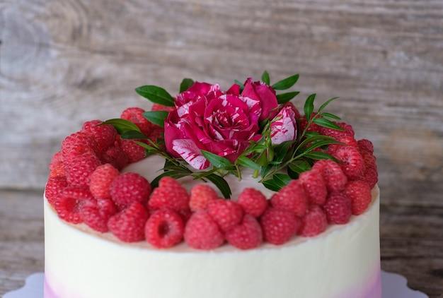 Festosa bella torta fatta in casa con crema bianca e viola, decorata con bacche di lampone e rosa rossa viva
