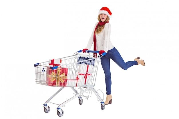Festosa bionda spingendo il carrello pieno di regali