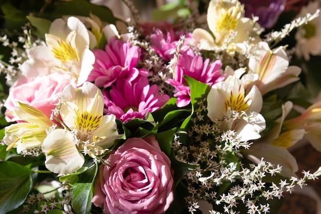 Un festoso bouquet di rose e altri fiori estivi. sfondo di fiori