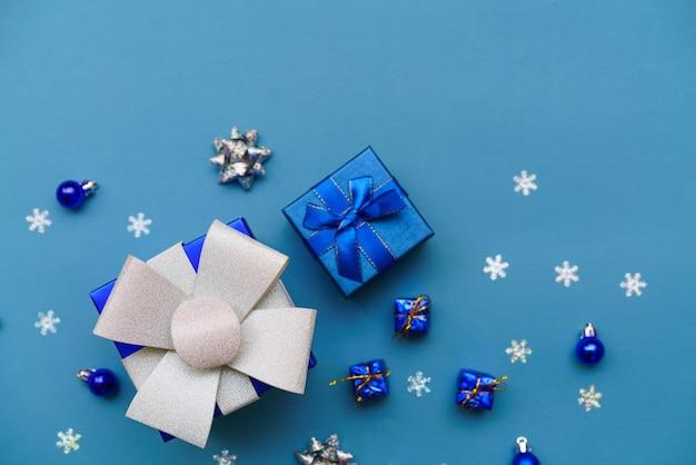 Scatola festiva da vicino fiocco blu su sfondo blu con palle di natale e fiocchi di neve capodanno cristo...