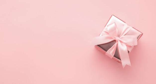 Scatola festiva in confezione dorata con fiocco in raso rosa pastello