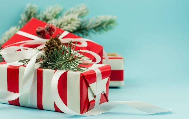 Scatole festive in confezione rossa con rami e coni, bacche e nastri su sfondo blu. angolo ravvicinato. il concetto di regali di capodanno.