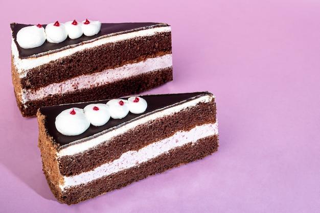 Torta festiva con strato di cioccolato e ricotta. due porzioni. su uno sfondo rosa. compleanno, vacanze, dolci. copia spazio.