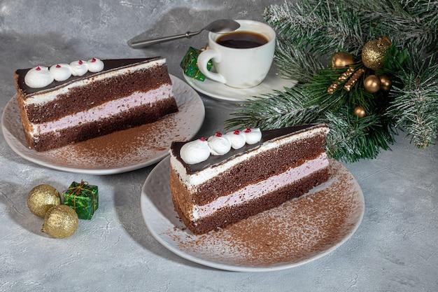 Torta festiva con cioccolato e intercalare croccante. due porzioni. su uno sfondo grigio. compleanno, vacanze, dolci. copia spazio.