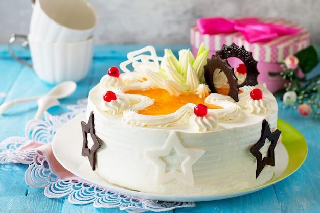 Una torta festiva con panna montata decorata con cioccolato e crema cremosa