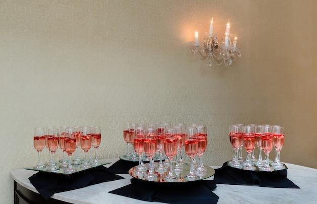 Flauti di champagne festosi pieni di spumante e fragole galleggianti romantiche luci scintillanti per le feste