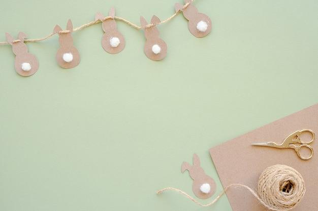 Decorazioni festive, per bambini o pasquali. ghirlanda di coniglietto di pasqua e carta kraft, filo di iuta, forbici e uova di quil su sfondo verde.