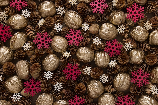 Sfondo di natale festivo con molti oggetti pigne nelle quali, noci dorate, fiocchi di neve rossi e bianchi.