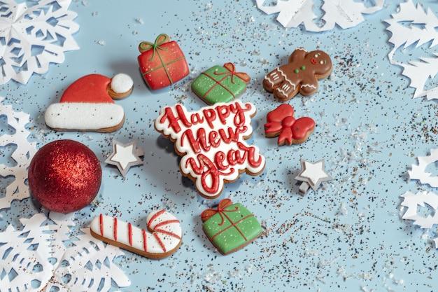Sfondo di natale festivo con fiocchi di neve di carta, pan di zenzero glassato di pan di zenzero, vista dall'alto di elementi di arredo. concetto di natale.