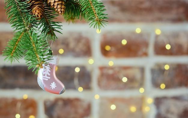Cartolina di natale festiva con un ramo di un albero di natale con un giocattolo sul tavolo di un muro di mattoni decorato con una ghirlanda, fuoco selettivo.