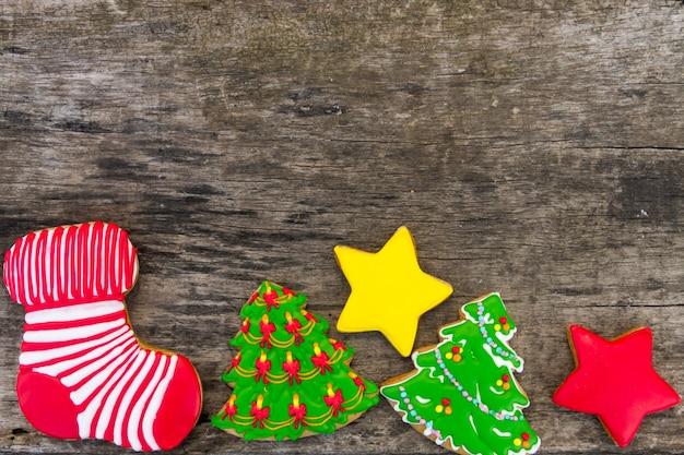 Biscotti natalizi a forma di albero di natale, stella e calzino di natale. pan di zenzero saporiti sulla tavola di legno rustica. vista dall'alto