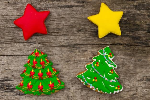 Biscotti natalizi a forma di albero di natale e stelle. pan di zenzero saporiti sulla tavola di legno rustica. vista dall'alto