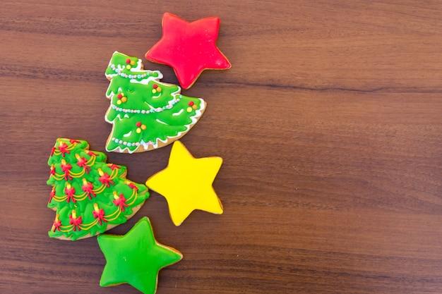 Biscotti natalizi a forma di albero di natale e stelle. pan di zenzero saporiti sulla tavola di legno. vista dall'alto