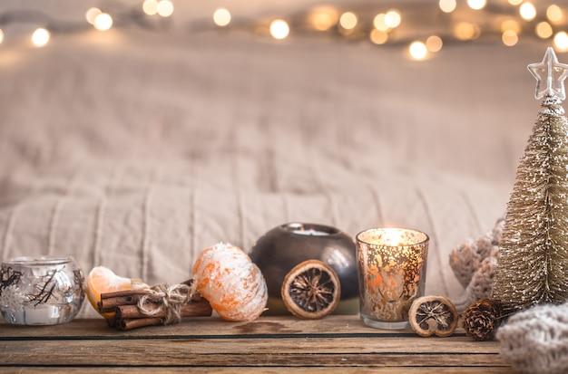 Atmosfera accogliente di natale festivo con decorazioni per la casa e mandarini su uno sfondo di legno, concetto di comfort domestico