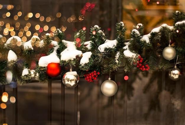 Decorazione festiva di natale di rami di abete con ghirlanda di bacche di palline nelle luci della sera