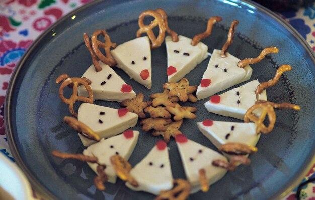 Dolce natalizio festivo con renne e microfono fatto di formaggio su un tavolo di legno