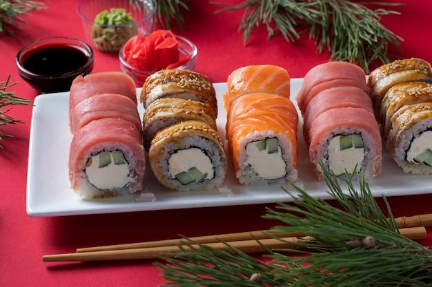 Cena di natale festiva con sushi di salmone, tonno e anguilla con formaggio filadelfia su piastra bianca su sfondo rosso. festa di fine anno. cibo asiatico
