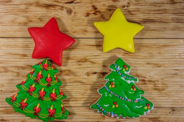 Biscotti festivi del pan di zenzero di natale sotto forma dell'albero di natale e delle stelle sulla tavola di legno. vista dall'alto