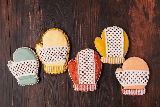 Festive natale e capodanno pan di zenzero a forma di guanto, piatto laici, su legno sfondo marrone.