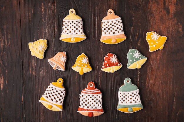 Un natale festivo e un pan di zenzero di capodanno a forma di campana, adagiato su uno sfondo marrone di legno.