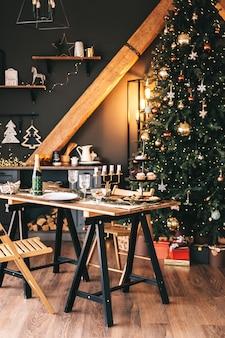 Tavola di natale festosa in cucina con un grande albero di natale e decorazioni.