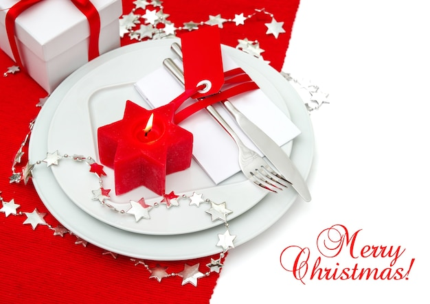 Decorazione festiva della regolazione del posto della tavola di natale in rosso e argento. cena a lume di candela. sfondo vacanze con testo di esempio buon natale!