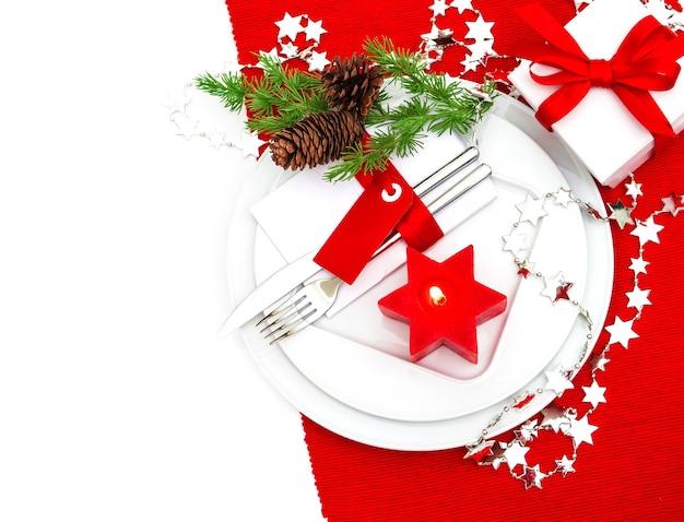 Decorazione festiva della regolazione del posto della tavola di natale in rosso e argento. cena a lume di candela. sfondo vacanze