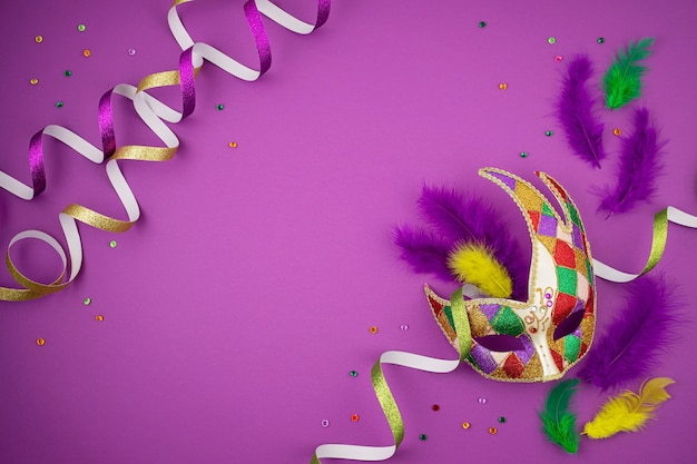 Festosa, colorata mardi gras o maschera di carnevale e accessori sul muro viola. appartamento laico, vista dall'alto, copia dello spazio