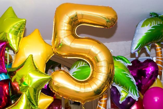 Composizione festiva di palloncini. numero aureo 5. stelle multicolori, cuori, palline rotonde.