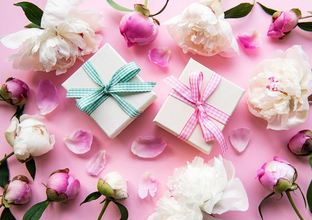 Composizione festiva su sfondo rosa pastello: fiori di peonie, scatole regalo. vista dall'alto, copia spazio.