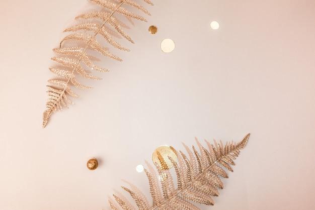 Composizione festiva. rami di felce floreale decorativo di natale lucido, coriandoli, luccica oro su fondo beige. lay piatto. copia spazio. composizione elegante in uno stile minimalista.