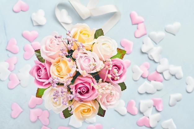 Composizione festiva con bellissimi fiori di rose delicate in scatola rotonda rosa su sfondo azzurro. lay piatto, copia dello spazio. biglietto d'auguri.