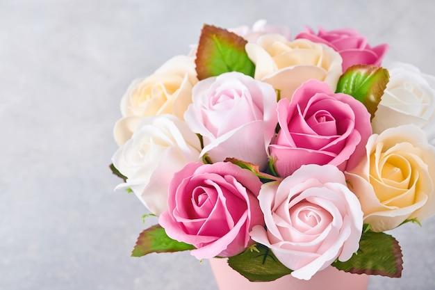 Composizione festiva con bellissimi fiori di rose delicate in scatola rotonda rosa su sfondo grigio chiaro. lay piatto, copia dello spazio.